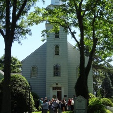 A front view of the Setauket Presbyterian Church on a busy Sunday morning. The current building dates from 1812, though the location (and graveyard) are original to the 18th century.