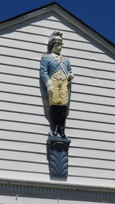 Above the side entrance of a local school is a painted wooden sculpture of Benjamin Tallmadge in his dragoon uniform.