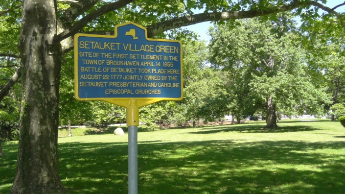 A photo of the blue historical marker on the present-day Setauket Green.